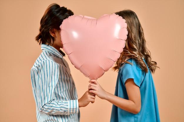 Ein süßes reizendes mädchen mit locken in einem blauen kleid und einem netten jungen in einem hemd hält einen valentinstag-herzballon isoliert