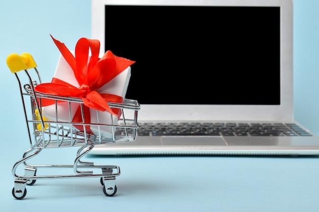 Ein supermarktwagen mit einem geschenk auf dem hintergrund eines laptops. online einkaufen. verkauf. geschenke für das neue jahr kaufen. platz kopieren. flache lage, ansicht von oben.