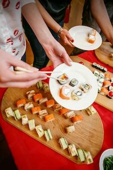 Ein sushi-mittagessen, sushi im teller, hände mit stäbchen