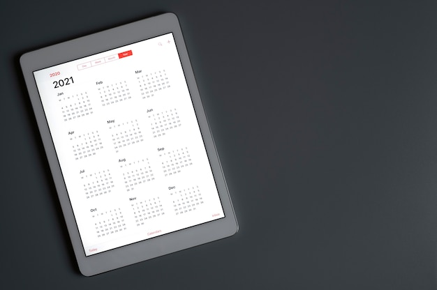 Ein tablet mit einem offenen kalender für 2021 jahre auf einem dunkelgrauen hintergrund. ein tablet mit einem offenen kalender für 2021 jahre auf einem dunkelgrauen hintergrund. platz für text