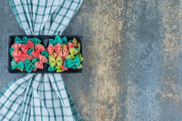 Ein tablett mit bunten farfalle-nudeln auf dem handtuch auf dem marmorhintergrund.