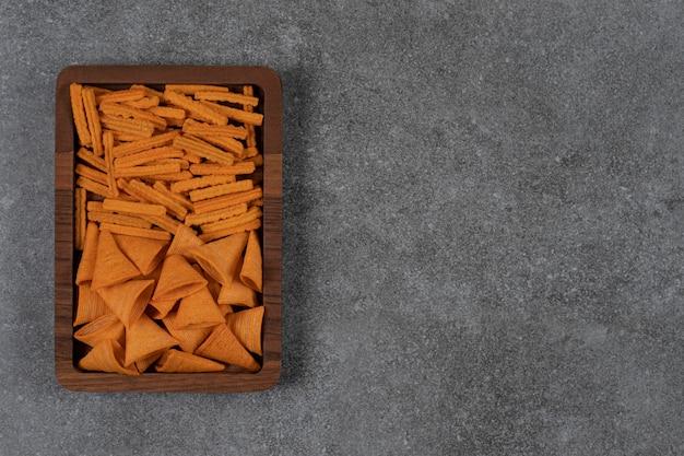 Ein tablett mit corn chips und getrocknetem brot auf der marmoroberfläche