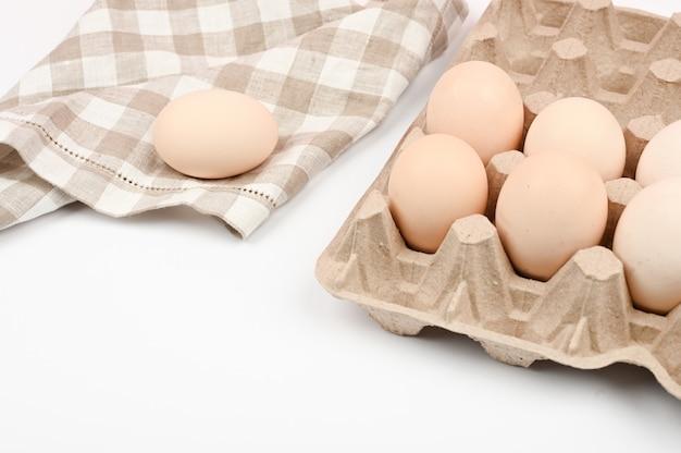 Ein tablett mit eiern auf einem weißen tisch. öko-tablett mit eiern auf weißem hintergrund, der trend des minimalismus, draufsicht. eierablage