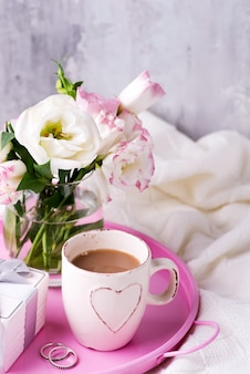 Ein tablett mit einer tasse kaffee, einer geschenkbox, blumen und ringen auf dem bett.