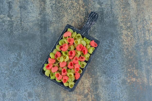 Ein tablett mit kochfertigen nudeln auf der marmoroberfläche.