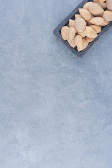 Ein tablett mit leckeren mandeln auf dem marmorhintergrund.