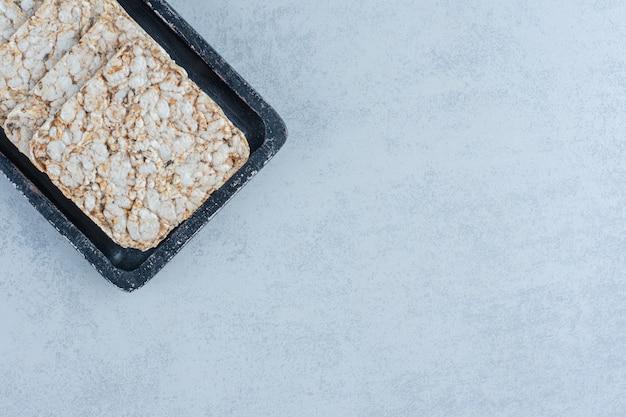 Ein tablett mit puffreiskuchen auf marmor.