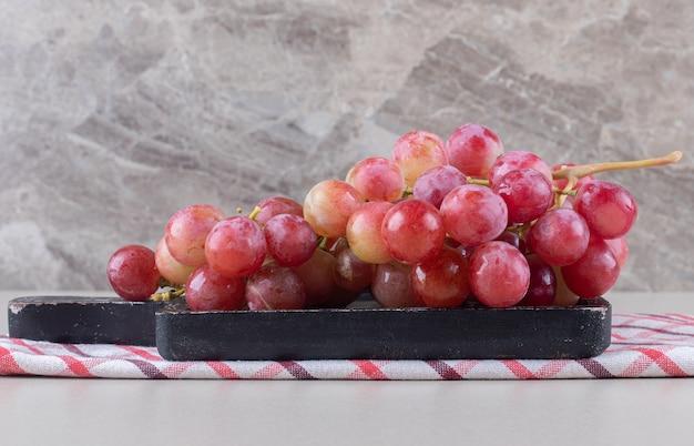 Ein tablett mit roten trauben auf einem handtuch auf marmor