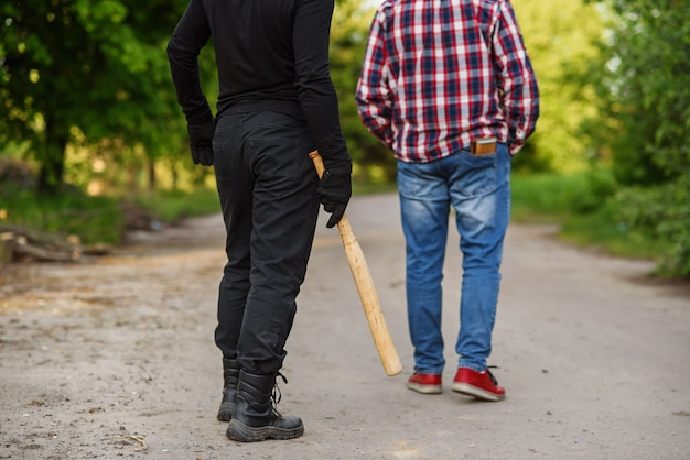 Ein täter in schwarzer kleidung mit einem baseballschläger in den händen greift einen mann an. taschendiebstahl auf der straße tagsüber.