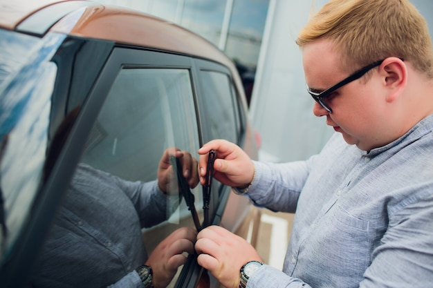 Ein täter in schwarzer kleidung und maske versucht, ein auto auf dem parkplatz zu stehlen. stoppen sie die kriminalität.