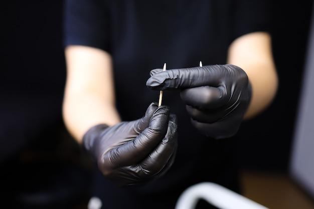Ein tätowierer mit schwarzen handschuhen hält einen zahnstocher vor sich und wickelt watte darum