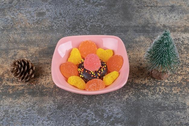 Ein tannenzapfen, eine schüssel mit süßigkeiten und eine baumfigur auf holzoberfläche