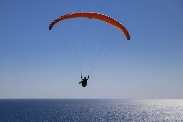 Ein tapferer mann fliegt an einem sonnigen tag mit einem gleitschirm über das offene meer.