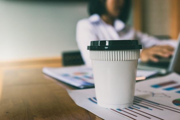 Ein tasse kaffee auf berichtspapier mit geschäftsfraushintergrund.