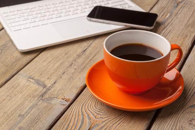 Ein tasse kaffee auf der orange platte auf dem holztisch. büroeinrichtung