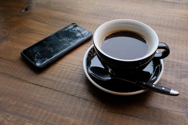 Ein tasse kaffee auf einem holztisch im café. in der nähe des telefons. unternehmen.