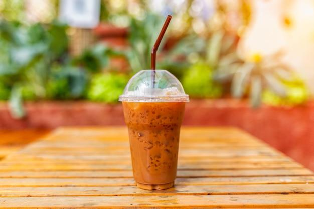 Ein tasse kaffee auf einem holztisch im garten und im sonnigen baumhintergrund