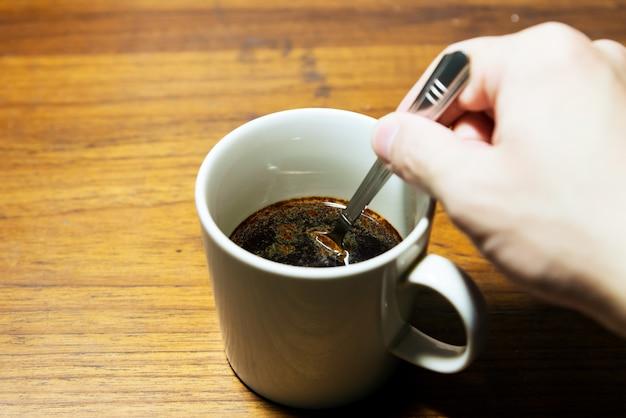 Ein tasse kaffee auf hölzernem hintergrund und einer hand, die einen löffel mit kopienraum hält