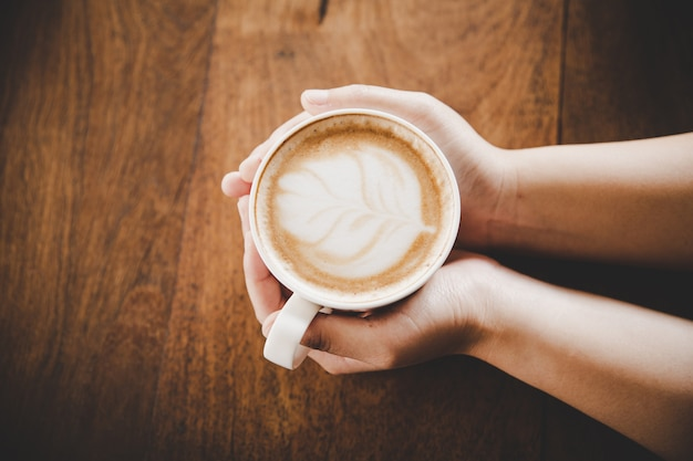Ein tasse kaffee in der hand von frauen auf hölzerner beschaffenheit.