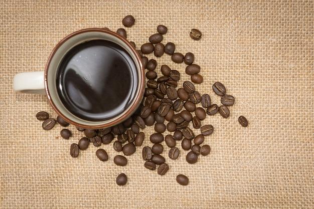 Ein tasse kaffee mit kaffeebohnen auf hanfsack, draufsicht