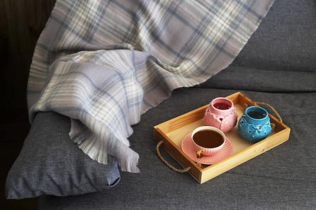 Ein tasse kaffee mit milch auf einem hölzernen tablett mit rosa und türkiskerzenständern