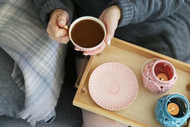 Ein tasse kaffee mit milch in den weiblichen händen auf einem hölzernen behälter