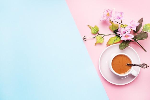 Ein tasse kaffee mit milch und niederlassung mit blumen und blättern auf einem rosa pastellhintergrund mit kopienraum. flach liegen.