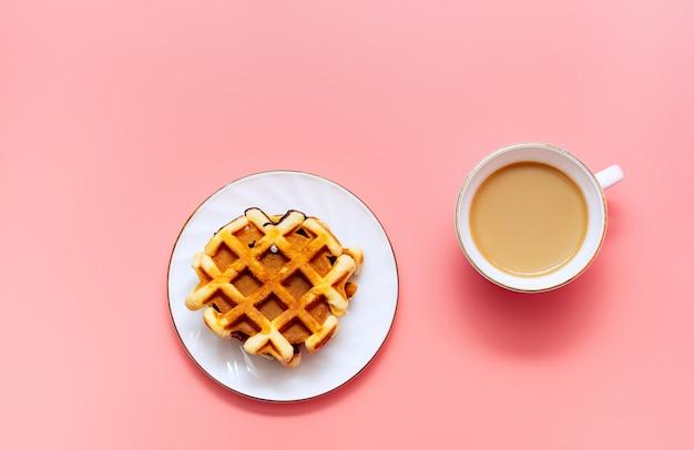 Ein tasse kaffee mit milch und selbst gemachten waffeln auf einem rosa hintergrund. leckeres frühstück minimalismus