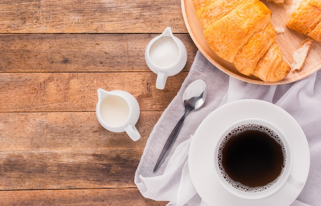 Ein tasse kaffee mit milch-, zucker- und hörnchenbrot auf holztisch, draufsicht