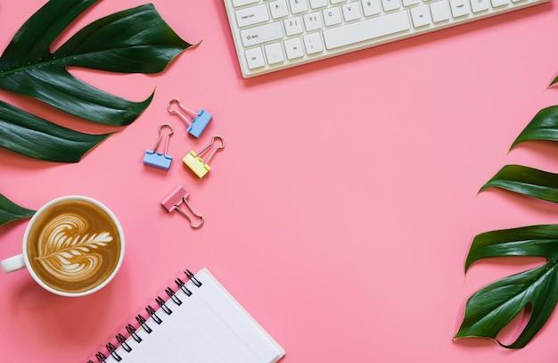 Ein tasse kaffee mit tastatur- und exemplarplatz auf rosafarbenem hintergrund. schreibtisch und getränkekonzept.