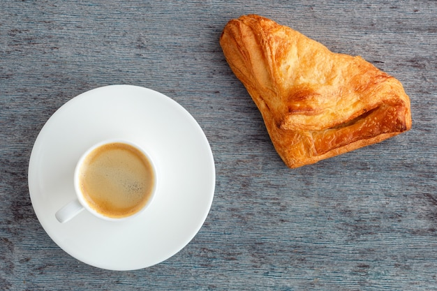 Ein tasse kaffee und ein brötchen auf einem hölzernen hintergrund