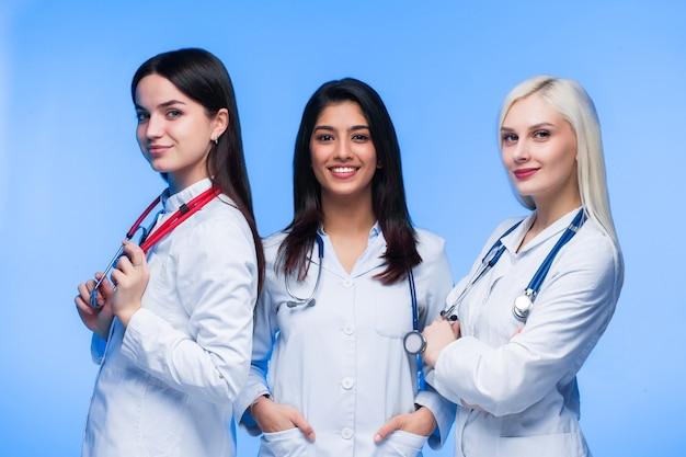 Ein team junger ärzte. multinationale menschen - arzt, krankenschwester und chirurg im blauen hintergrund. eine gruppe von medizinstudenten verschiedener nationalitäten schaut in die zelle.