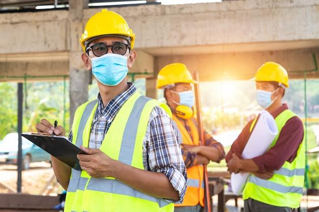 Ein team von bauingenieuren und drei architekten ist bereit, medizinische masken zu tragen