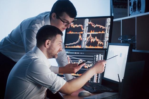 Ein team von börsenmaklern unterhält sich in einem dunklen büro mit bildschirmen. analysieren von daten, grafiken und berichten für investitionszwecke. kreative teamwork-händler