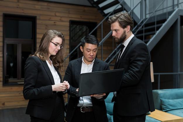 Ein team von drei mitarbeitern diskutiert ein projekt