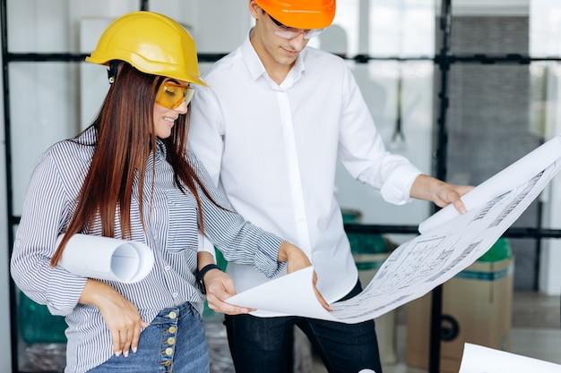 Ein team von ingenieuren arbeitet im büro und überprüft zeichnungen