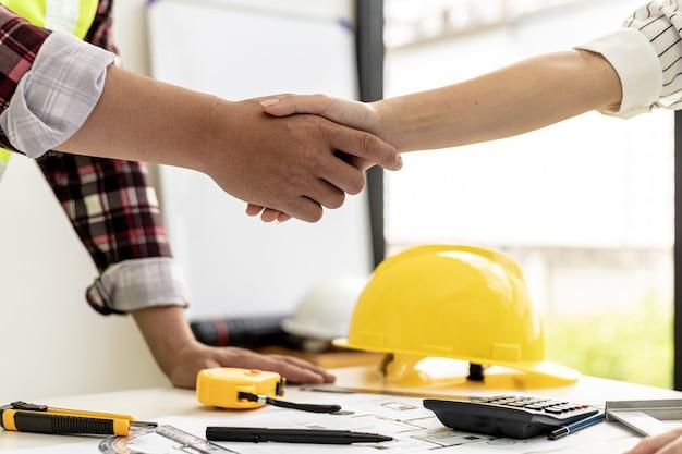 Ein team von ingenieuren und architekten reicht sich die hand, nachdem es gemeinsam ein haus für einen kunden entworfen hat, treffen sich zusammen, um den bau zu planen und einige der entwürfe zu ändern. design- und einrichtungsideen.