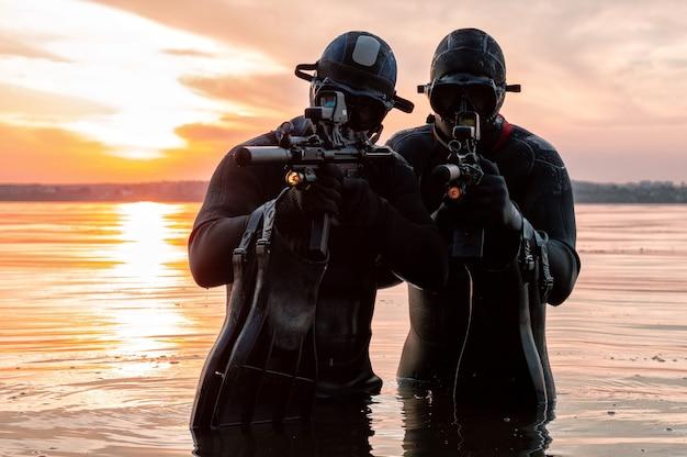 Ein team von kämpfern einer spezialeinheit bewegt sich auf dem wasser, um die aufgabe zu erfüllen. das konzept der instabilität, militäroperationen, der kalte krieg. gemischte medien
