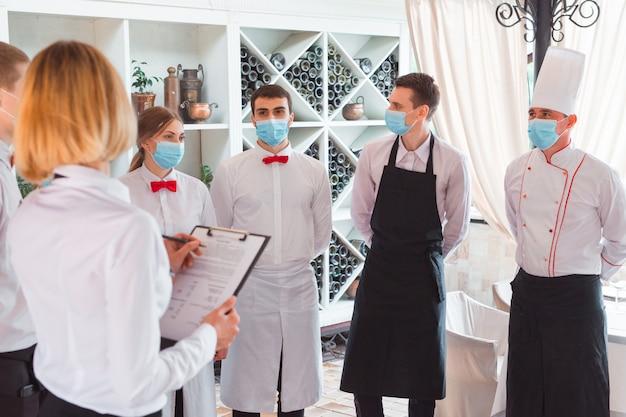 Ein team von kellnern führt ein briefing auf der sommerterrasse des restaurants durch.