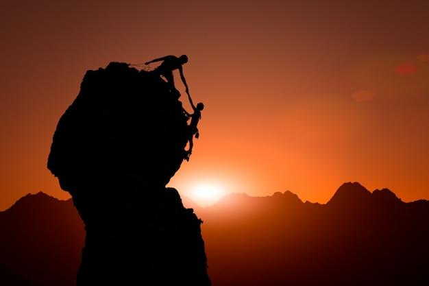 Ein team von kletterern hilft bei sonnenuntergang, den gipfel zu erobern