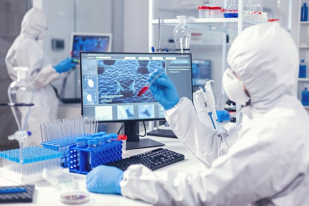 Ein team von medizintechnikern testet blut, um im wissenschaftlichen labor ein heilmittel für coronavirus zu finden. arzt, der mit verschiedenen bakterien und geweben arbeitet, pharmazeutische forschung für antibiotika gegen covid19.