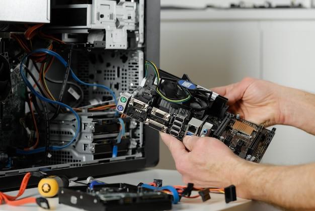 Ein techniker hält das motherboard in einem desktop-gehäuse.