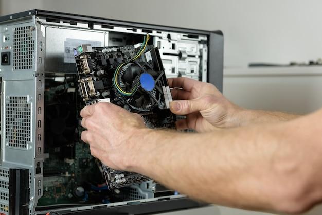 Ein techniker installiert das mainboard im desktop-gehäuse aus nächster nähe