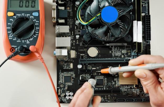 Ein techniker überprüft die funktionsfähigkeit des computer-motherboards aus nächster nähe