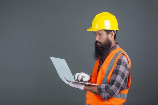 Ein technikmann, der einen gelben sturzhelm hält ein notizbuch auf einem grau trägt.