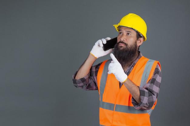 Ein technikmann, der einen gelben sturzhelm hält ein telefon auf einem grau trägt.