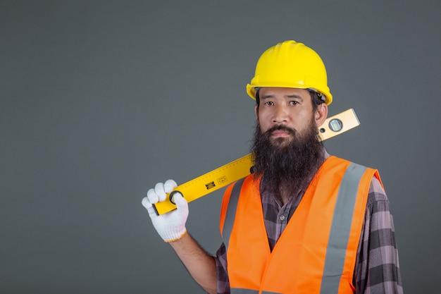 Ein technikmann, der einen gelben sturzhelm hält einen wasserstandsmesser auf einem grau trägt.