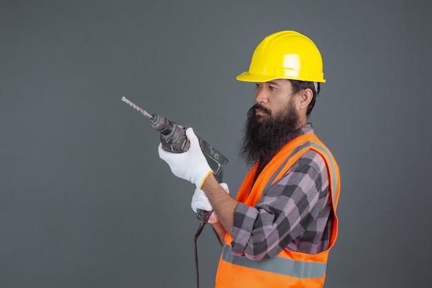 Ein technikmann, der einen gelben sturzhelm mit baugeräten auf einem grau trägt.