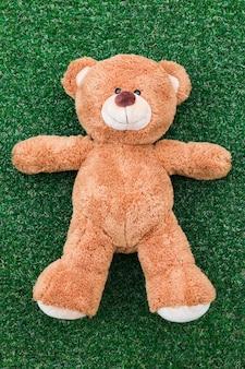 Ein teddybär auf einem grünen grashintergrund