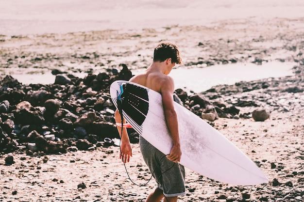 Ein teenager betritt das wasser mit seinem surftisch unter dem arm, bereit zum surfen - aktive sportler gehen zum training am wasser